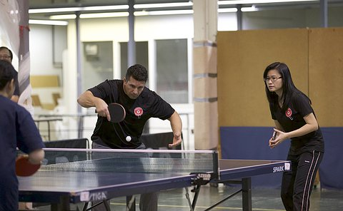 A man hits a table tennis ball across a table beside a woman holding a table tennis paddle