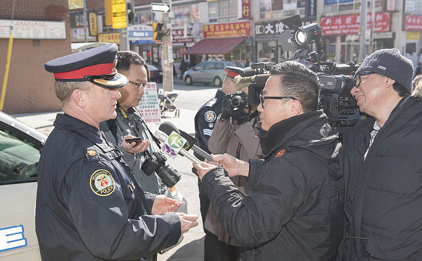 A man in TPS uniform speaks to people with microphones and cameras