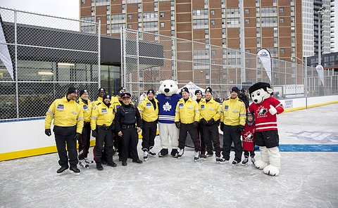 A group of men and women in TPS uniform with a Maple Leaf mascot and others on an outdoor ice rink
