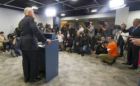 Chief Bill Blair standing at the podium of the Toronto Police Headquarter's Media gallery
