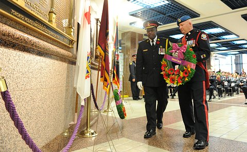 Two men in TPS uniform holding a wreath