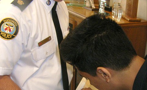 A teenage boy signs the back frame of a painting while a man in TPS uniform holds the work