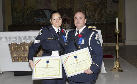A man and woman in TPS uniform hold framed certificates