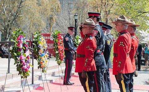 men in RCMP uniforms saluting