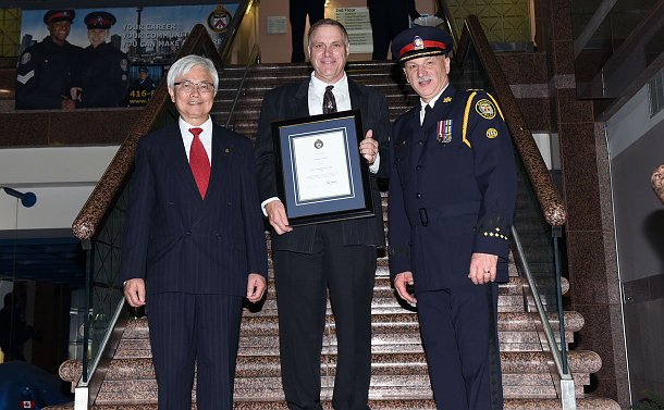 A man in a suit holding an award plaque is flanked by a man in a suit and another man in a police uniform