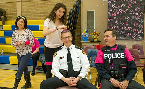 an officr in uniform sitting on a chair getting his hair dyed pink by a student.