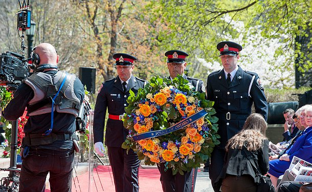 Three officers walking, the middle one carrying a wreath.