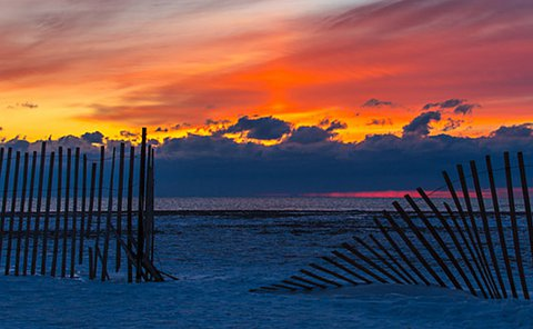A broken snowfence in the foreground with a sunrise in the background over the lake