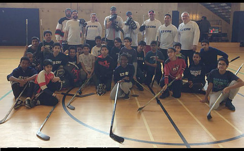 A group of kids and adults with hockey sticks in a gym