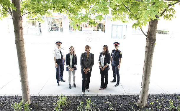 A group of women, two in TPS uniform standing on a sidewalk