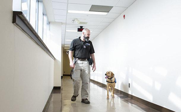 A man walking with a dog in a hallway