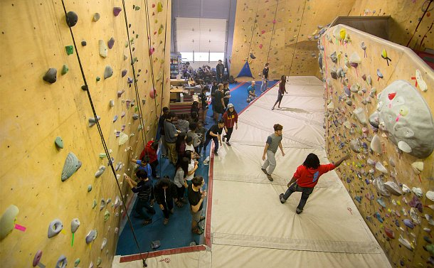 A view from above as a group looks on as a person walks to a climbing wall