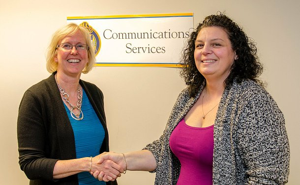 "Two woman shaking hands, behind them is a sign that reads ""communications"""