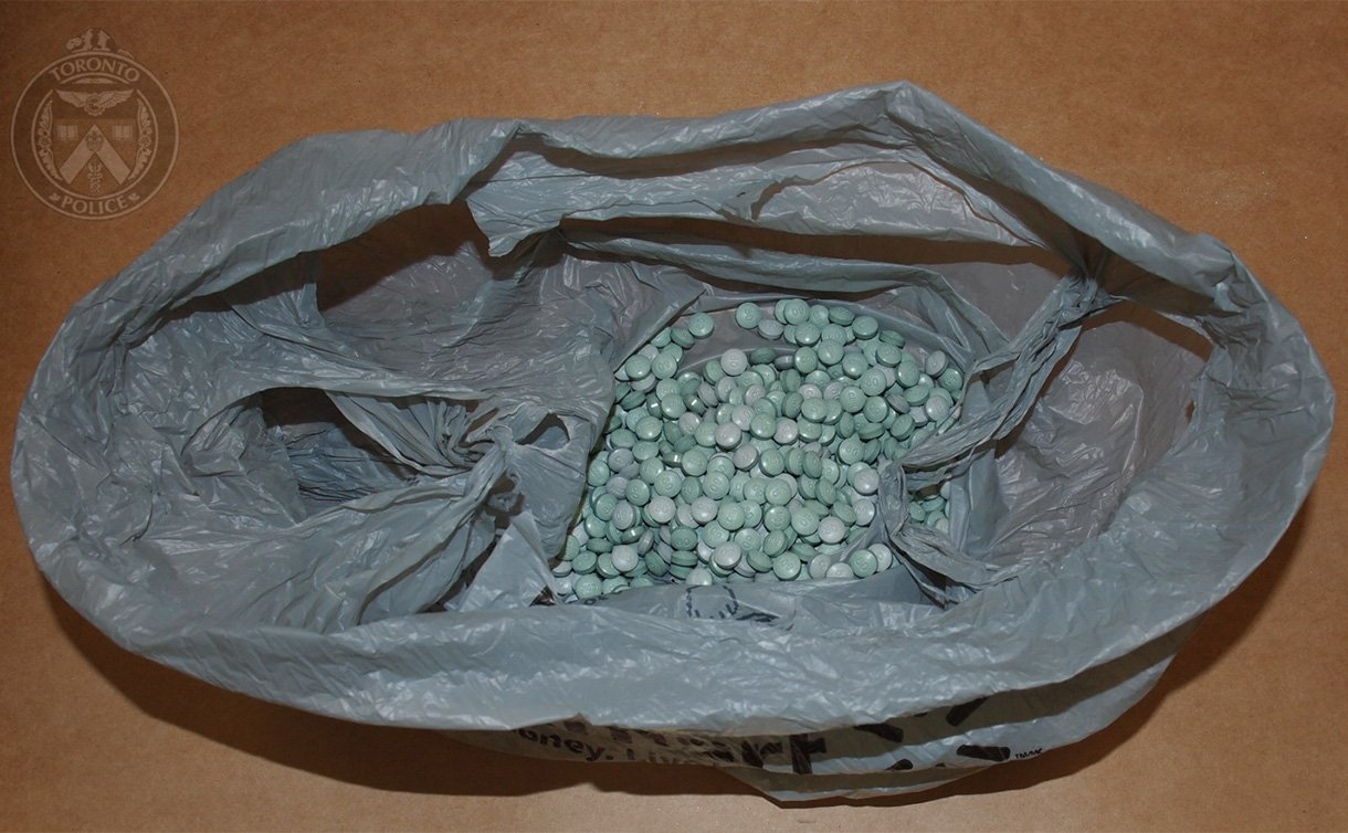Photo of small blue and green pills in a plastic bag
