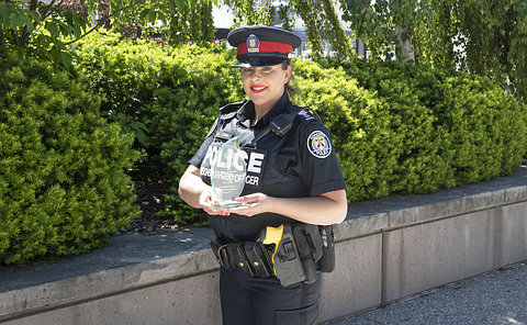 A woman in TPS uniform holding a glass award