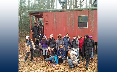 A group of girls on and near a railway caboose