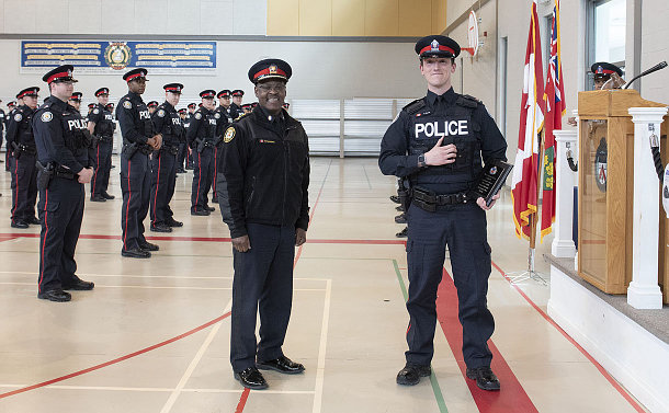 Two men in TPS uniform, one holds plaque