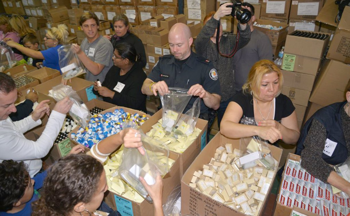 Men and women form an assembly line putting items from boxes into clear bags