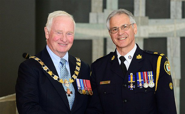 Two men stand together, one wearing chains of office, another in TPS uniform