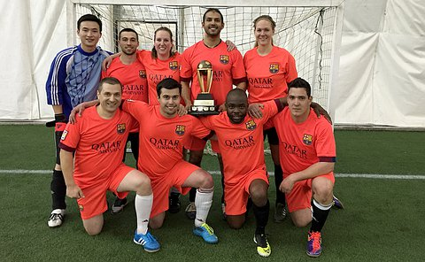 Men and women in soccer uniforms posing with a trophy in a indoor soccer field.