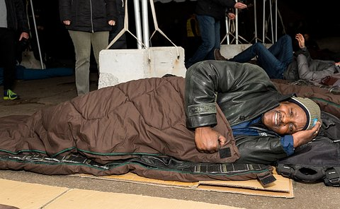 Th chief in a brown sleeping bag and toque lying on top of a piece of cardboard