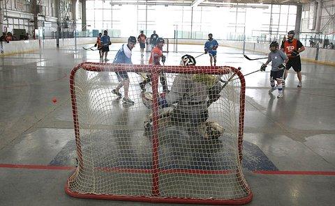 View from behind net of goalie saving an orange ball as other players run toward net