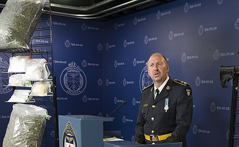 A man at a podium in OPP uniform behind a table with guns on it