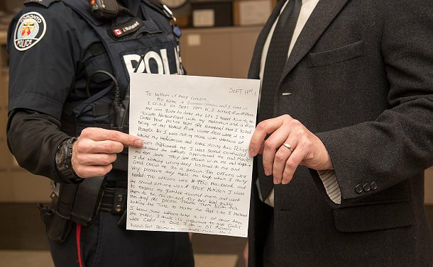 A shot of a hand written letter, two people are holding it, you can see in the background that one has a uniform on.