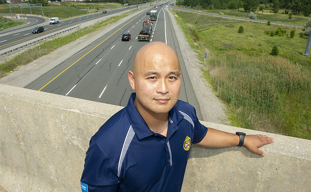 A man standing at a highway overpass