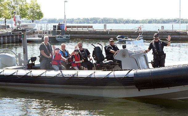 Several adults, some in police uniforms, and two boys, on a boat leaving a marine