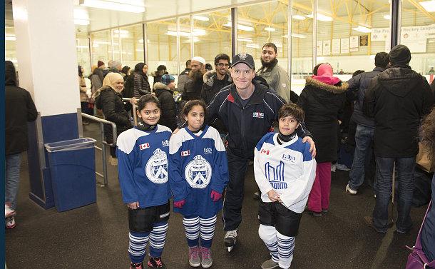 A man with three girls in hockey uniform