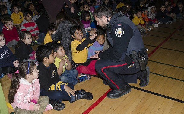 A man in TPS uniform kneels in front of a large group of children seated on a school floor