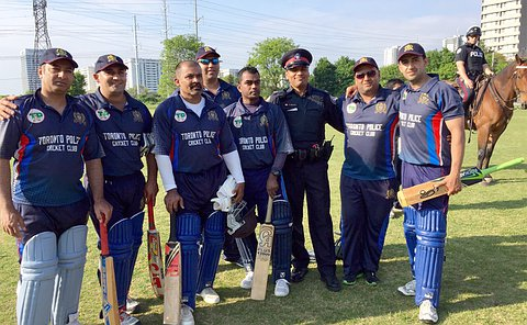 A group of men in TPS cricket uniforms and TPS uniforms, including an officer on a horse