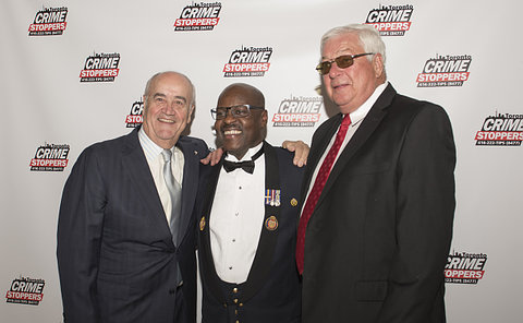 Three men in front of a Crime Stoppers backdrop
