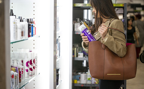 A woman putting an aerosol can in her purse