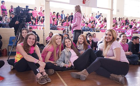 A group of girls sitting in a school gym, a reporter holds a microphone behind them looking at a camera