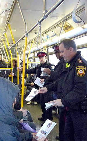 Several men in TPS and TTC uniform hand out brochures to people on a bus