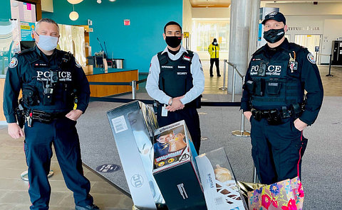 Two officers with a security guard and toys