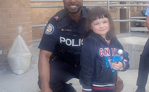 A man in TPS uniform kneels beside a girl