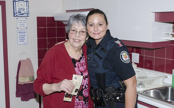 One woman holding two one hundred dollar bills and another in a Toronto police uniform stand in a kitchen