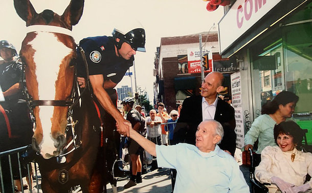A man in a wheelchair shaking hands with a police officer on a horse