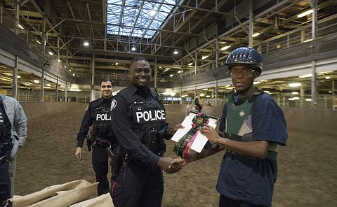 Two men in TPS uniform, one offers a handshake to a boy