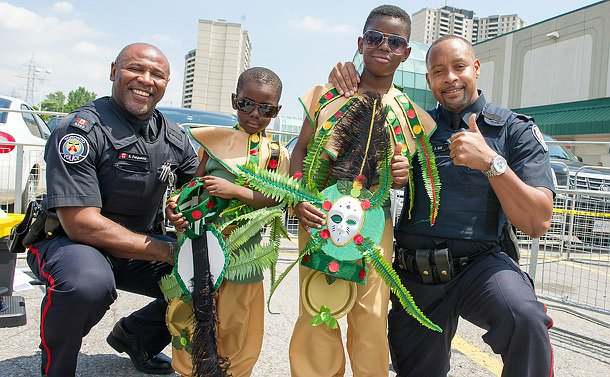 Two Toronto Police Officers pose with two young boys in costumes. The officer on the far right is giving a thumbs up towards the camera.