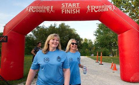 Two women run across towards a finish line
