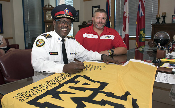 A man in TPS uniform signs a flag with a man seated next to him
