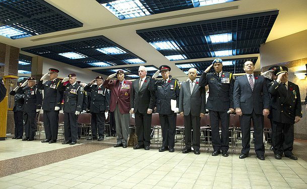 A line of officers and civilians stand, with uniform officers saluting