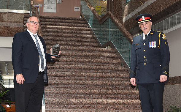 Two men stand apart, one with glass award