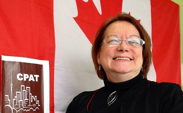 A woman stands beside a Canadian flag