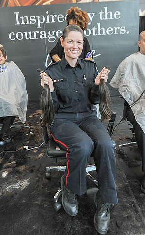 A woman in TPS uniform with a shaved head sitting in a chair holding two ponytails of hair