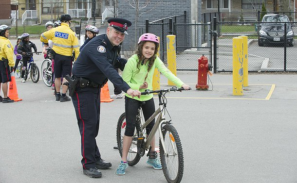 A man in TPS uniform with a girl on a bicycle